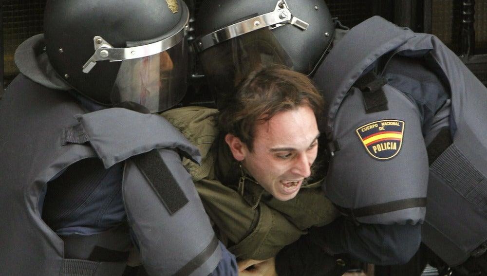 Efectivos de la Policía Nacional sujetan a una de las personas que hoy querían evitar el desahucio de una familia de Torrejón de Ardoz