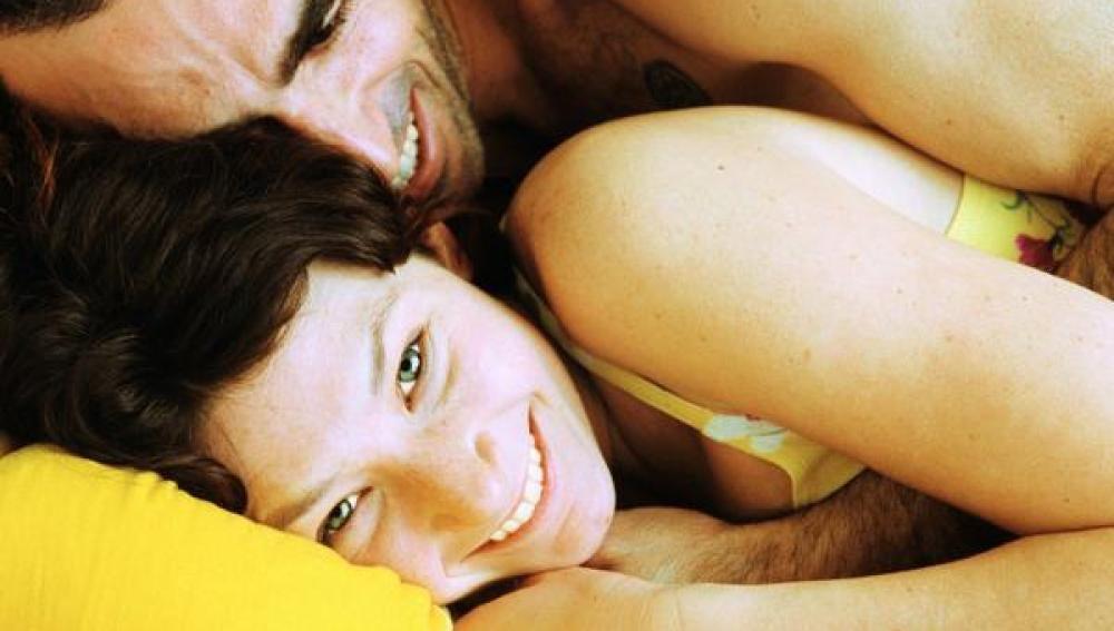 Una pareja bromea tumbada en una cama