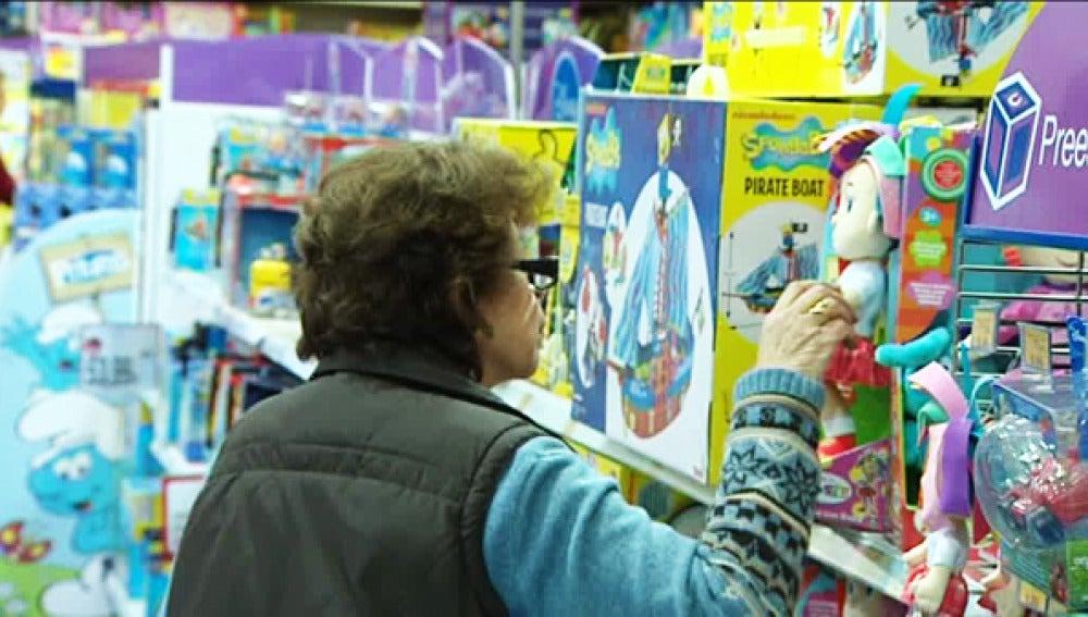 Una señora elige juguetes en una estantería.