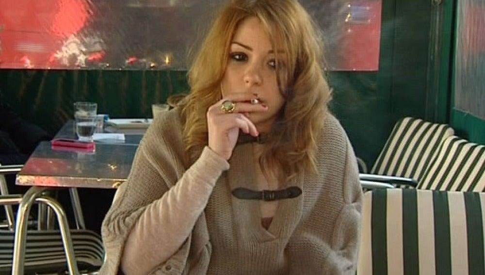 Una joven fuma en la terraza de un restaurante