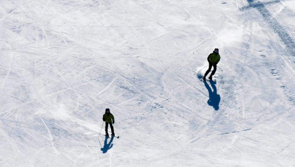 Dos esquiadores descendiendo una pendiente