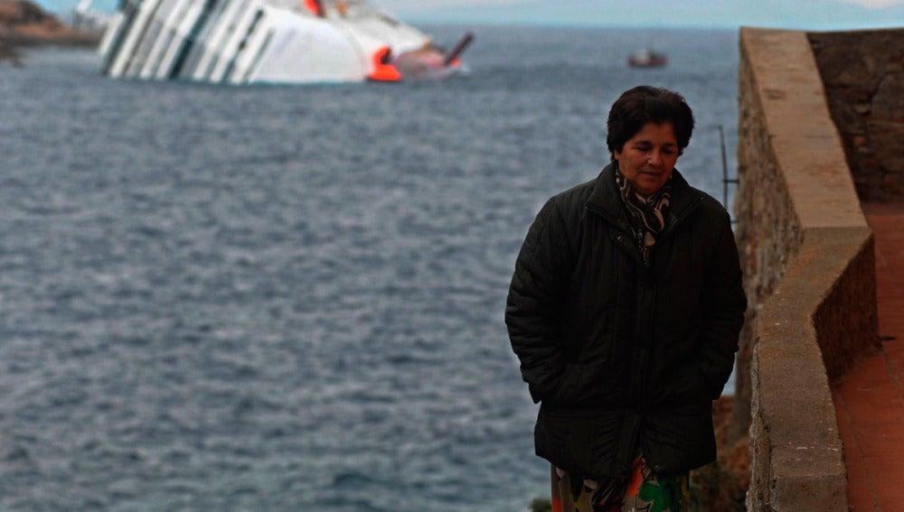 Una mujer en la isla de Giglio con el crucero Costa Concordia a su espalda