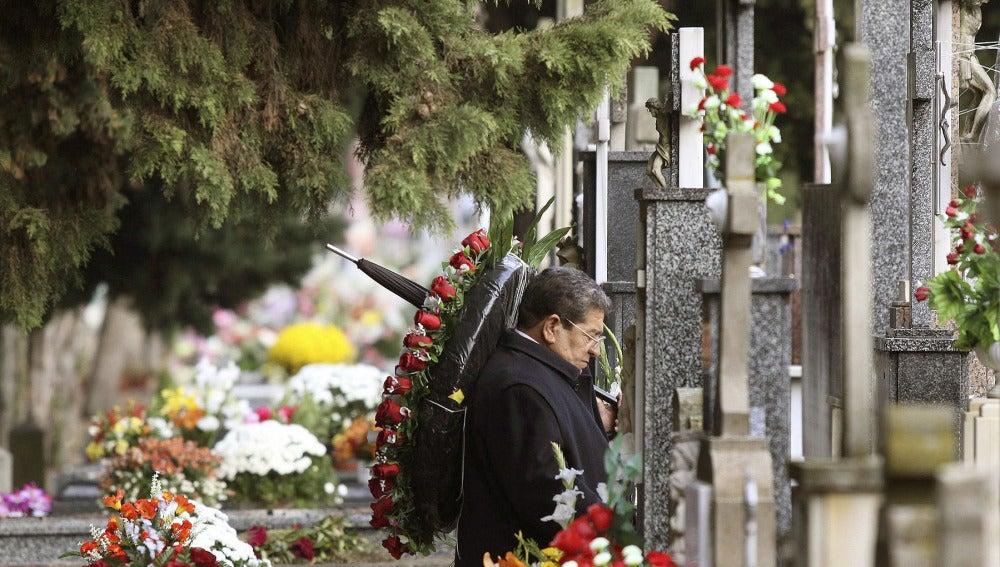 Un hombre ante una tumba en un cementerio