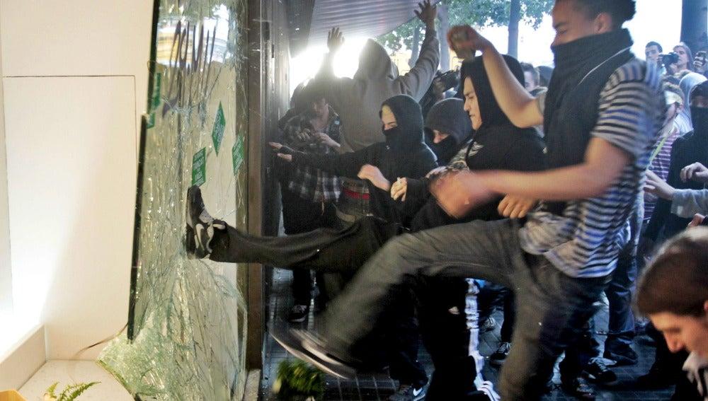 Un grupo de manifestantes rompe un escaparate en Barcelona
