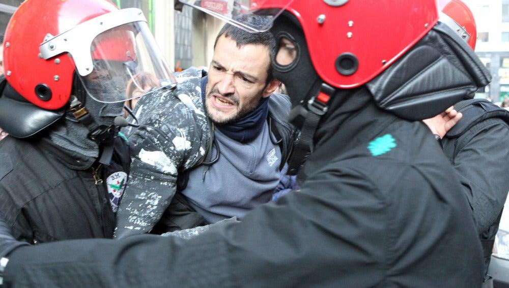Un piquetero forcejea con agentes de la Ertzaintza en Bilbao