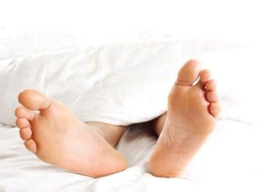 Un hombre descansa tumbado en una cama