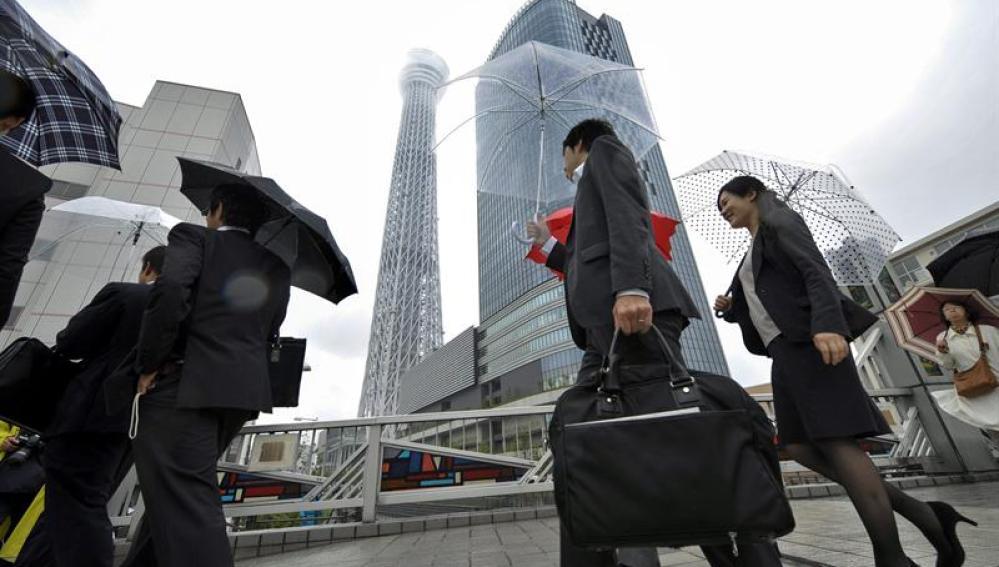 Japoneses que van a su trabajo con la torre de fondo