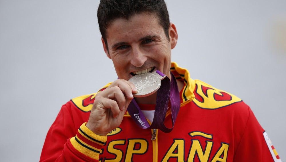 David Cal mordiendo la medalla de plata