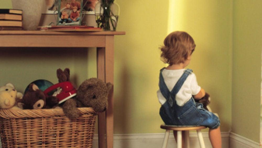 Niño castigado frente a la pared