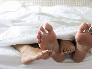 Pies de una pareja en una cama