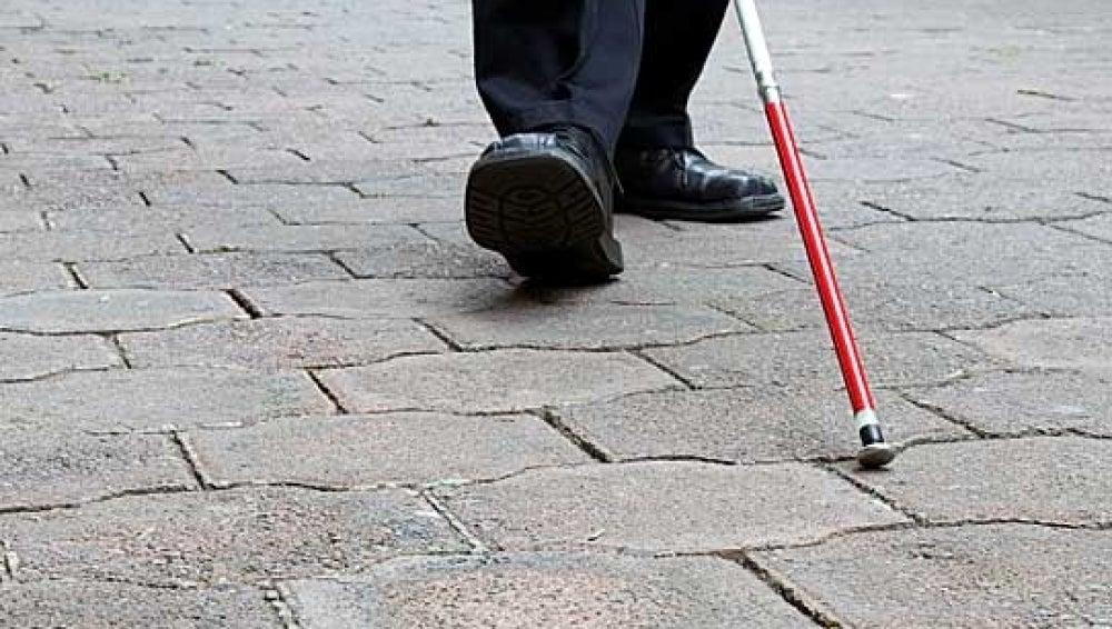 Un invidente camina con su bastón