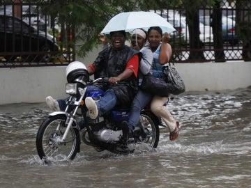 Tres personas se desplazan bajo la lluvia en Santo Domingo.