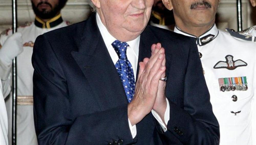 El rey de España, don Juan Carlos, saluda a un invitado antes de la cena que el presidente indio, Pranab Mujerjee