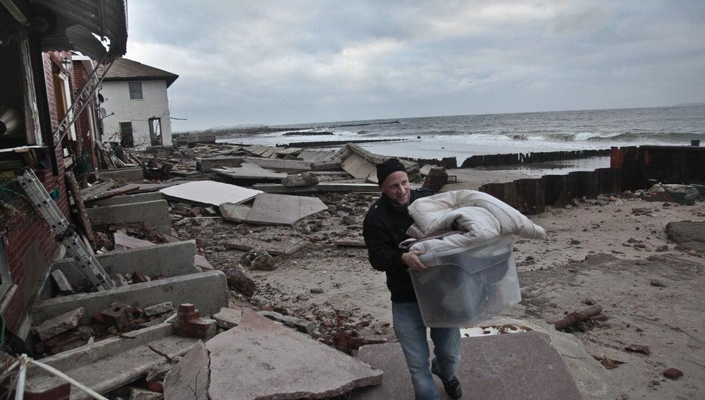 Un hombre recoge sus pertenencias tras el paso de Sandy
