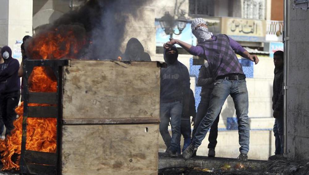 Unos palestinos lanzan piedras a los soldados israelíes en el Hebrón, Cisjordania