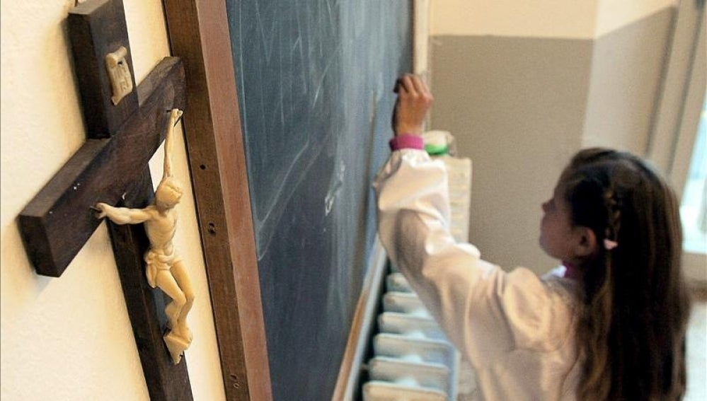 Una alumna escribe en la pizarra de una clase en la que cuelga un crucifijo