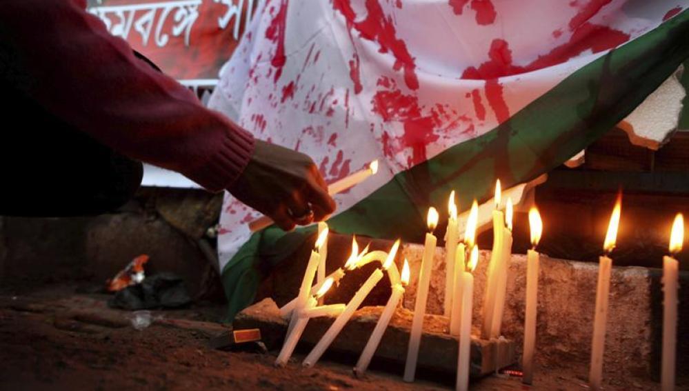 Una manifestante enciende una vela durante una protesta en contra de la salvaje violación de la joven