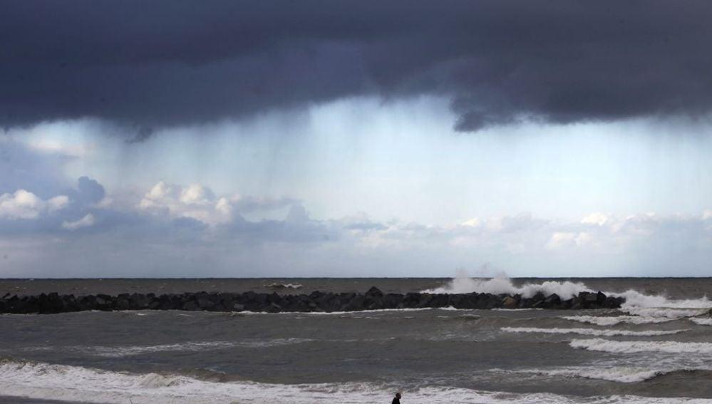 Un hombre camina por la playa de la Zurriola de San Sebastián