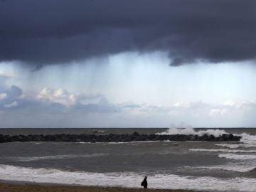 Un hombre camina por la playa de la Zurriola de San Sebastián antes de las lluvias