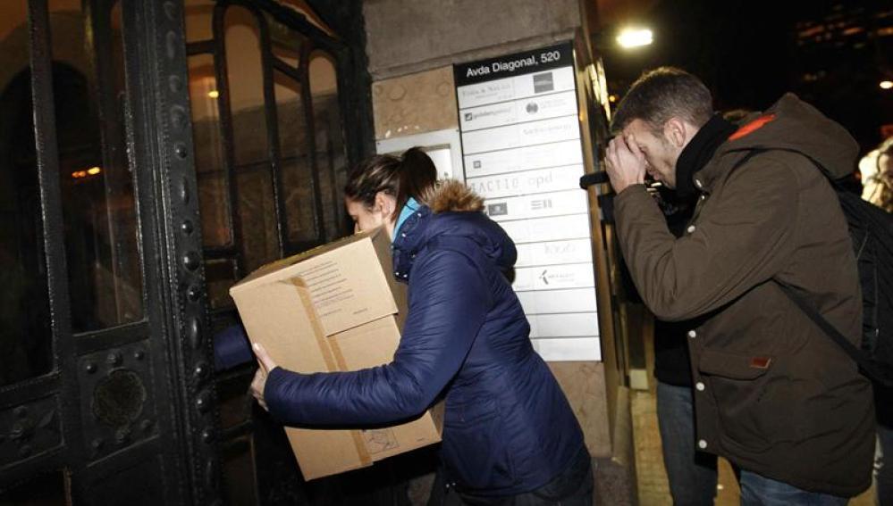 Miembros de la Policía Nacional llevan cajas a la sede central en Barcelona de la agencia de detectives Método 3