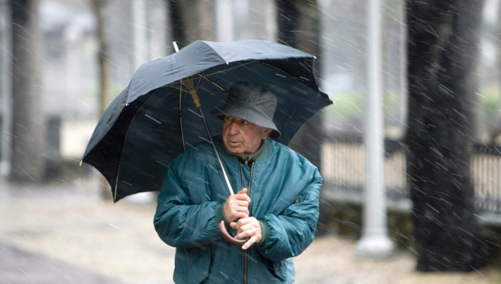 Un hombre se refugia de la lluvia en Vitoria