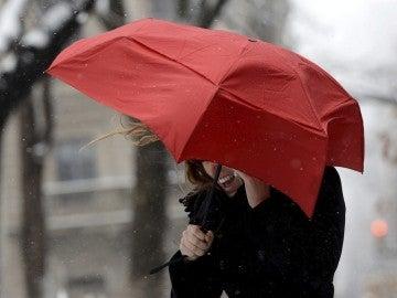 Una mujer habla por su teléfono móvil tratando de protegerse del viento