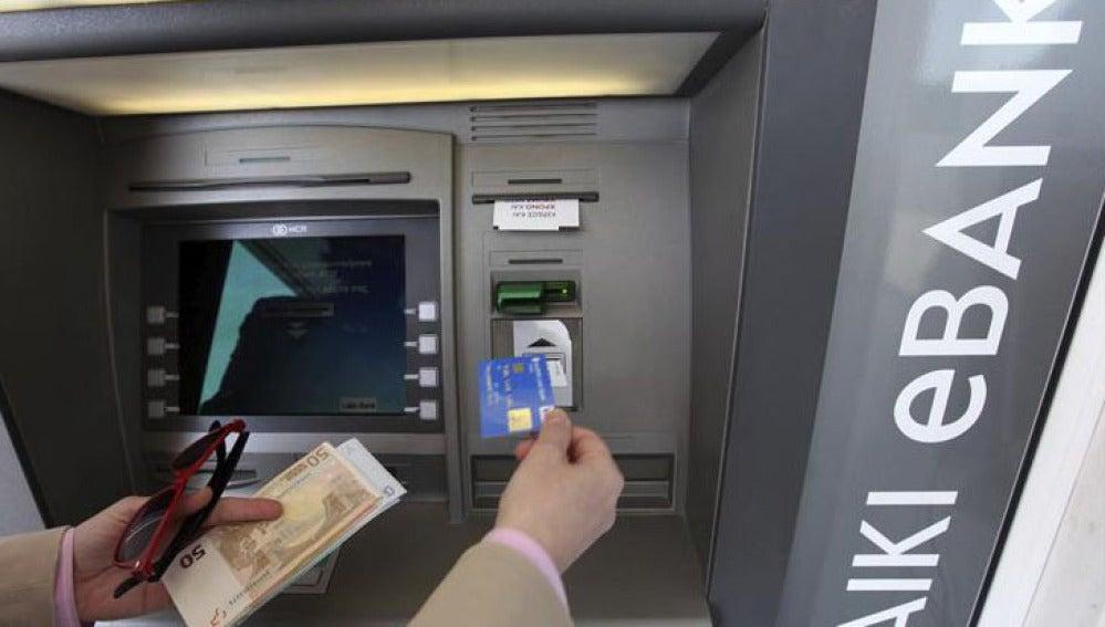 Un hombre saca dinero de un cajero automático en Nicosia