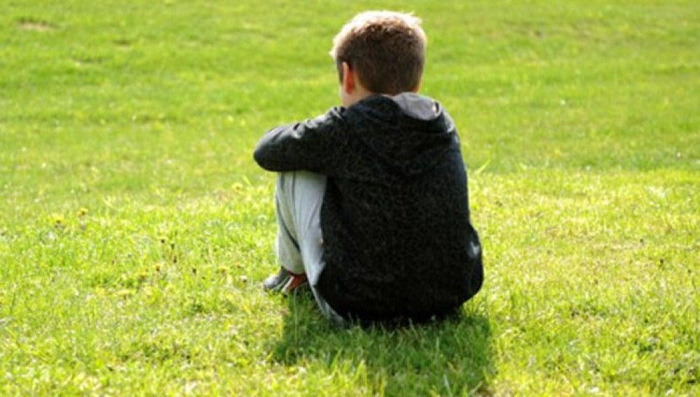 Imagen de archivo de un niño sentado en el césped.
