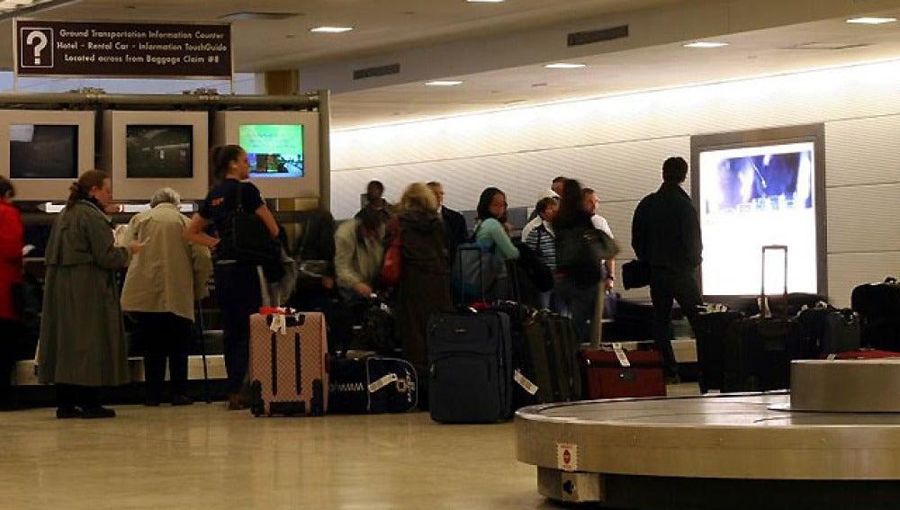 Pasajeros esperando con sus maletas