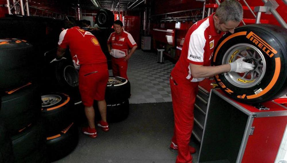 Mecánicos del equipo Ferrari trabajan con los neumáticos
