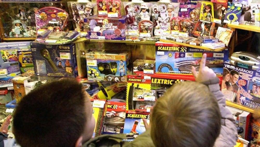 Unos niños miran un escaparate lleno de juguetes