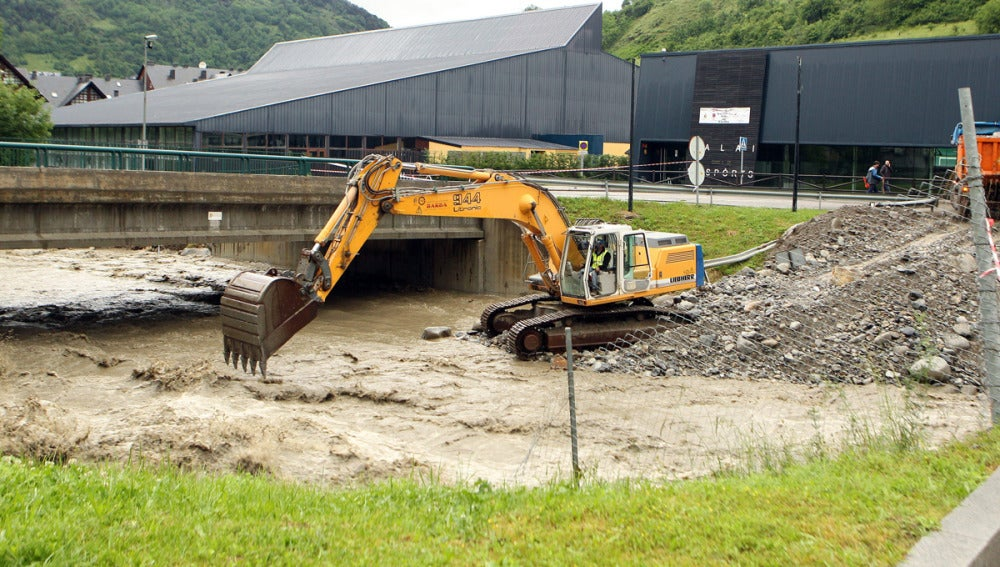 Una excavadora trabaja en el cauce del río Garona