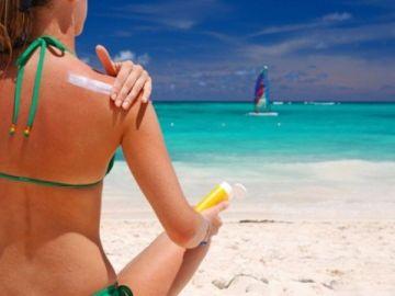 Mujer aplicándose crema solar
