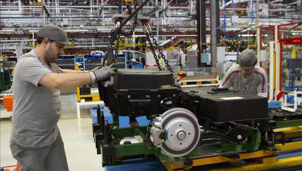 Dos operarios colocan baterías en un automóvil