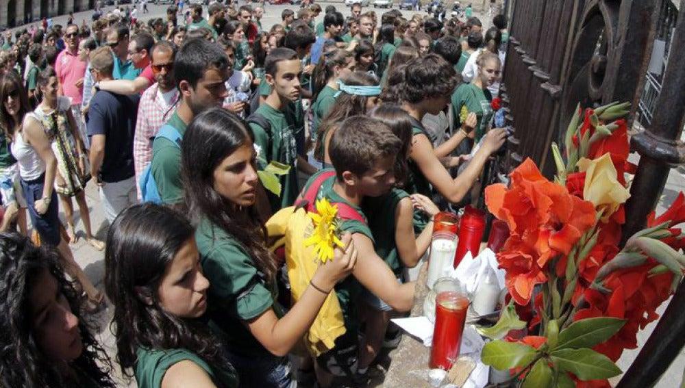 Los peregrinos depositan flores, velas y notas en la fachada de catedral de Santiago