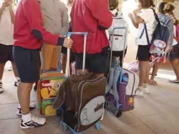 Varios niños llegan con sus mochilas al colegio.