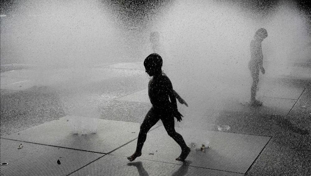 Un niño se refresca en una fuente
