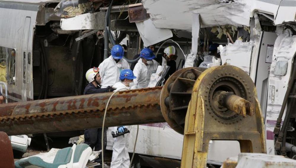 Agentes de la policía científica investigan y recogen datos del tren accidentado en Santiago