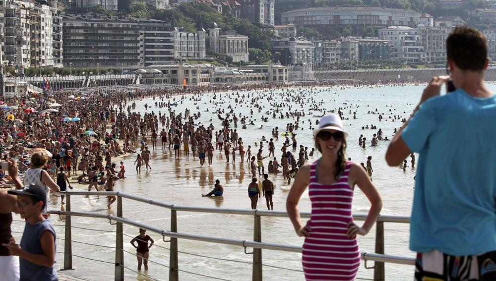 Dos turistas se fotografían junto a la playa de La Concha de San Sebastián.