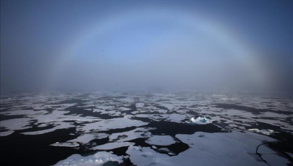 El arco iris apareciendo en el horizonte en el Ártico