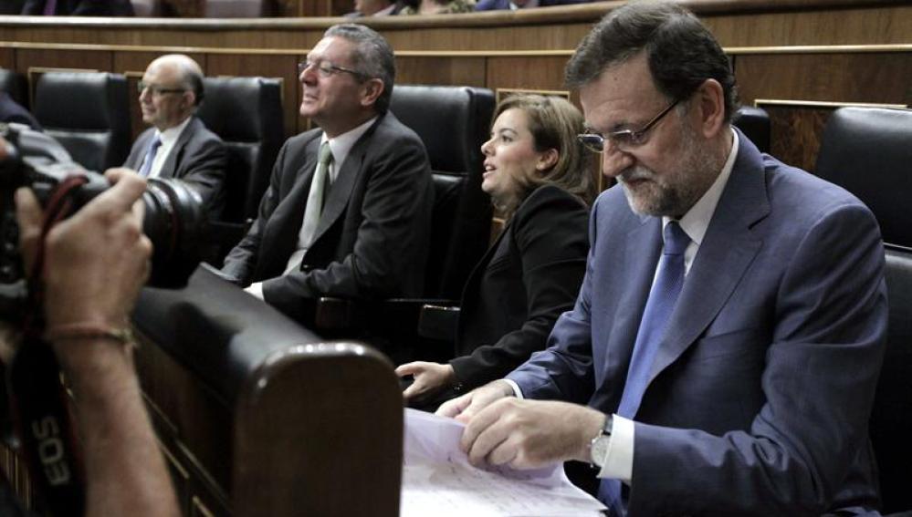 El presidente del Gobierno, Mariano Rajoy, repasa papeles en su escaño