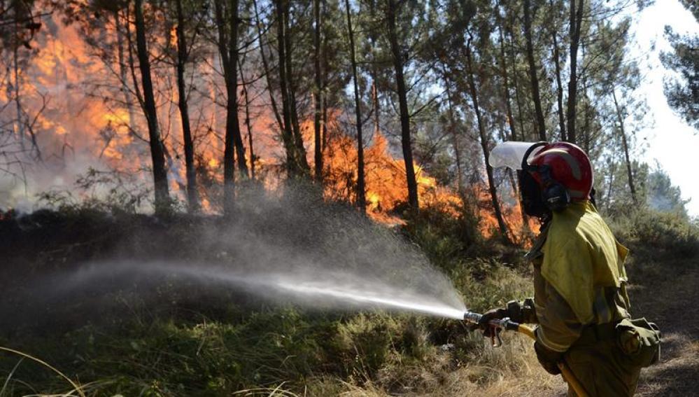 Un bombero intenta apagar una zona invadida por las llamas en A Merca