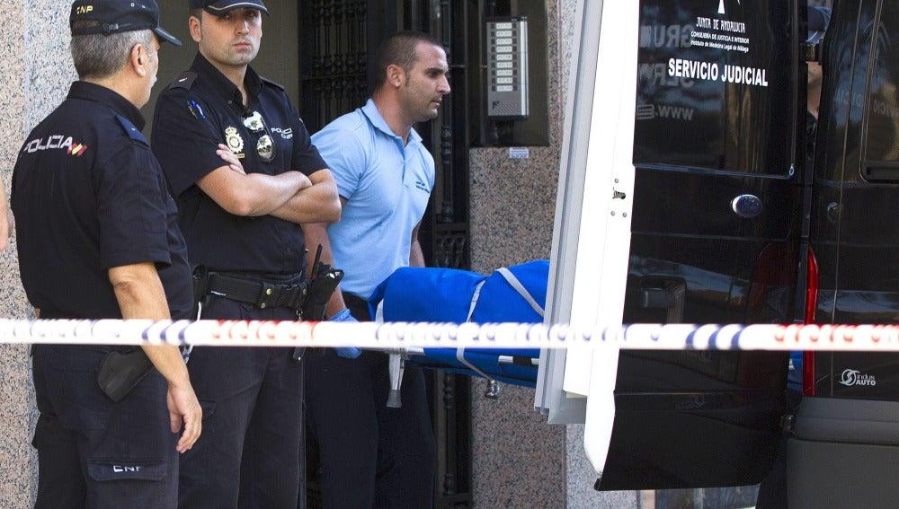 Efectivos de los servicios funerarios trasladan el cuerpo de una de las dos víctimas mortales