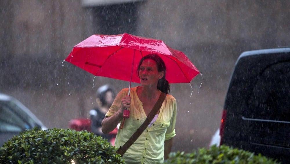 Una mujer pasea bajo la lluvia