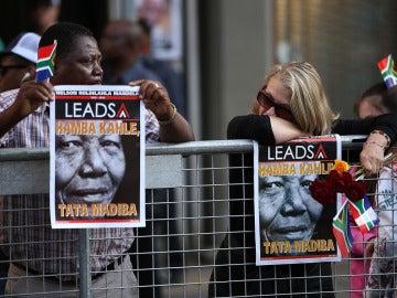 Dos ciudadanos sudafricanos esperan el paso del cortejo de Nelson Mandela en Pretoria