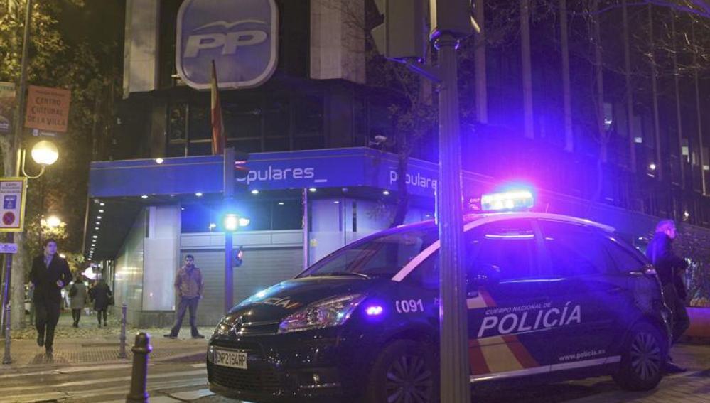 Un coche de la Policía estacionado en el exterior de la sede del PP
