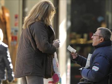 Una mujer compra a un vendedor ambulante un décimo de lotería de Navidad