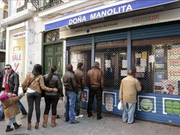 Varias personas permanecen en el exterior de una administración de lotería