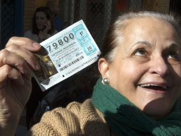 Una señora muestra su décimo premiado con un cuarto premio