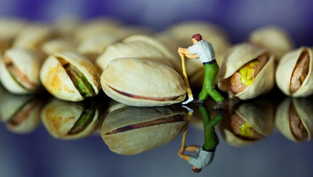 Un hombre intenta abrir una cáscara de pistacho